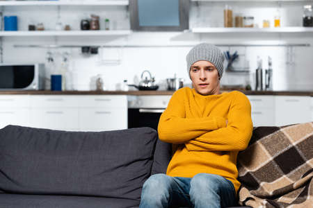 shivering man in knitted sweater and hat sitting on sofa with crossed arms in cold kitchen