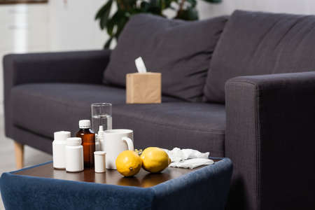 selective focus of medicines, fresh lemons and drinks on bedside table near gray sofa with paper napkins