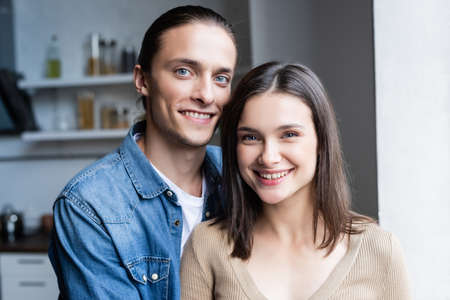 joyful couple looking at camera while standing together in kitchen Stockfoto