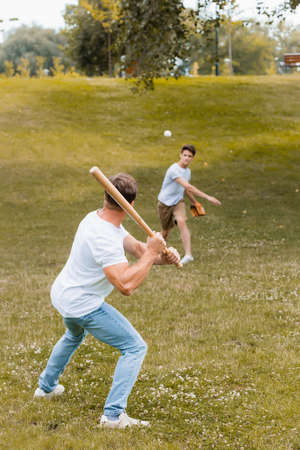 back view of father holding softball bat while playing baseball with teenager boy