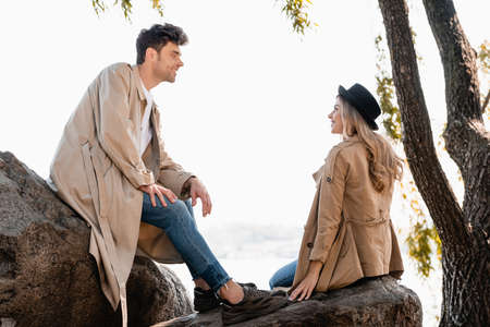 blonde woman in hat and man in trench coat sitting on stones and looking at each other