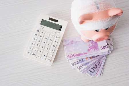Top view of piggy bank with bandage on money near calculator