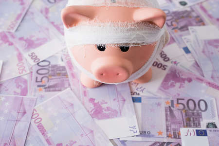 High angle view of piggy bank with bandage on money