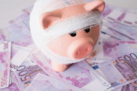 Selective focus of piggy bank with bandage on money