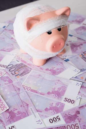 Selective focus of piggy bank on euro banknotes