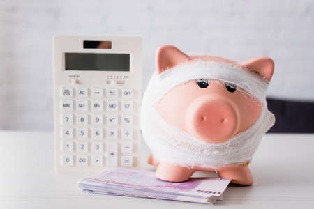 Selective focus of piggy bank near euro banknotes and calculator on white table