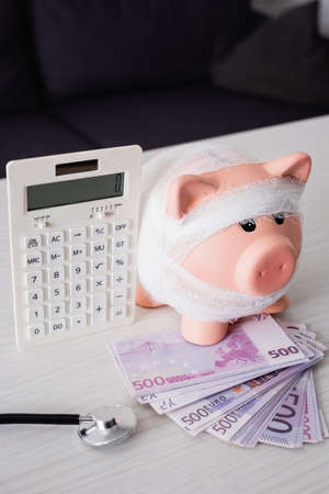 Selective focus of piggy bank with bandage on money near calculator