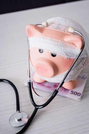 High angle view of piggy bank on table with stethoscope