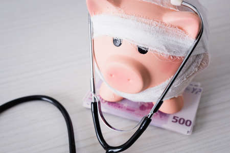 Selective focus of piggy bank on money with stethoscope on white table