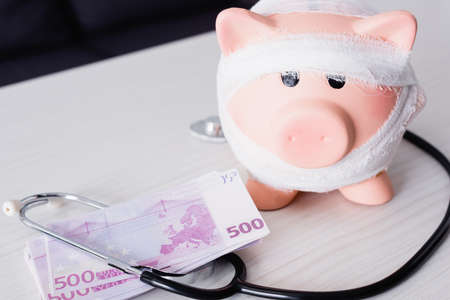 Selective focus of piggy bank near stethoscope and money on table Stock fotó