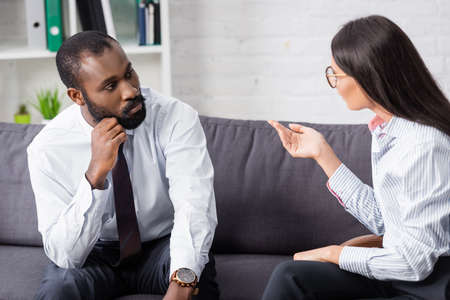brunette psychologist gesturing while talking to concentrated african american man holding hand near face Banco de Imagens