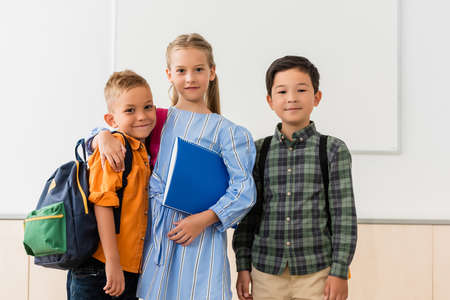 Schoolgirl with notebook embracing classmate near asian friend in classroom Stock Photo