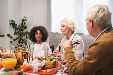 selective focus of senior woman talking to multicultural family during thanksgiving dinner