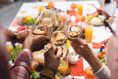 partial view of multiethnic relatives clinking wine glasses while celebrating thanksgiving day