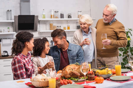 Selective focus of multicultural family celebrating thanksgiving near food on table
