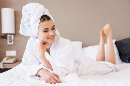 barefoot and pleased woman in towel and white bathrobe lying on bed in hotel room