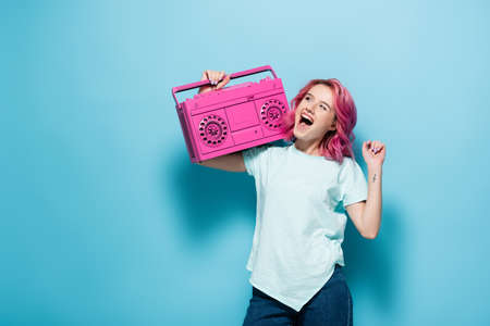 young woman with pink hair holding vintage tape recorder on blue background