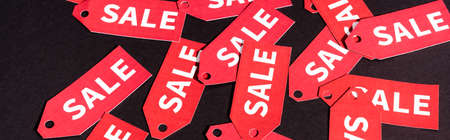 horizontal crop of red labels with sale lettering on black background