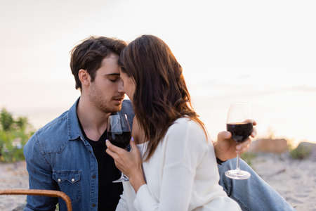 Young couple with glasses of wine kissing on beach at sunset Stockfoto