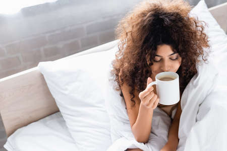 high angle view of young curly woman smelling coffee in bedroom