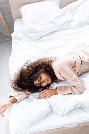 high angle view of curly and young woman with closed eyes sleeping on bed