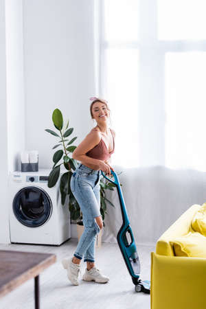 Modern housewife with vacuum cleaner looking at camera near plant and washing machine
