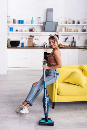 Housewife sitting on yellow couch and holding modern vacuum cleaner at home