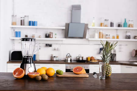 Fresh fruits on cutting board near glass and blender on kitchen table
