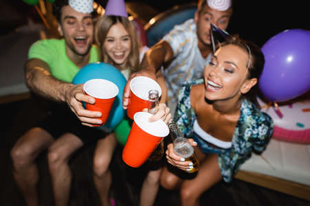 Selective focus of young friends in party caps clinking with beer and disposable cups at night Foto de archivo