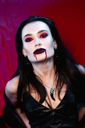 pale woman with blood on face looking at camera on red