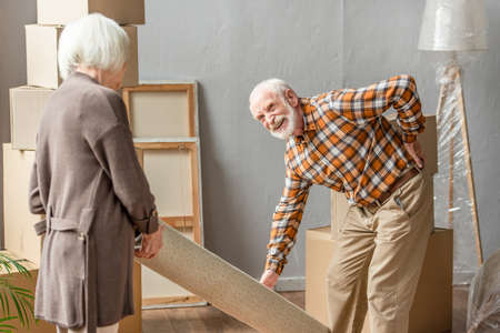senior man suffering from backache while rolling carpet with wife