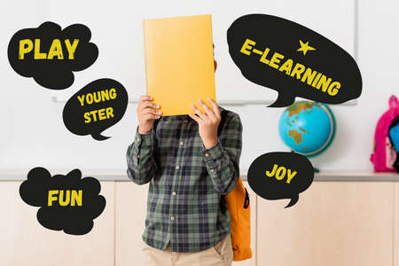 Schoolboy holding book near face and play, youngster and e-learning illustration
