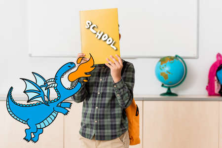 Schoolboy holding book near face and dinosaur illustration in school