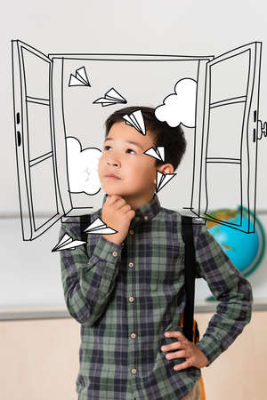 Dreamy asian schoolboy looking away near window and paper planes illustration 免版税图像