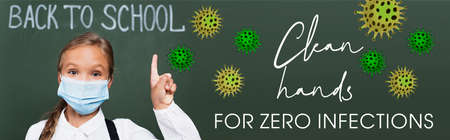 horizontal image of schoolgirl in medical mask pointing with finger near chalkboard and clean hands for zero infections lettering in classroom