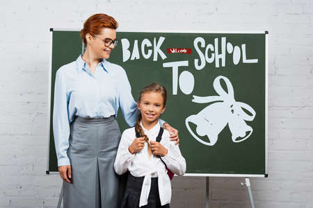 teacher and schoolgirl standing near chalkboard with back to school lettering 免版税图像
