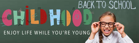 horizontal image of schoolgirl touching eyeglasses near chalkboard with back to school and childhood, enjoy life while you are young lettering