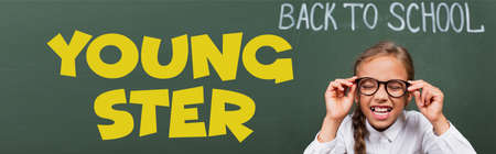 horizontal image of schoolgirl with closed eyes touching eyeglasses near chalkboard with back to school and youngster lettering in classroom