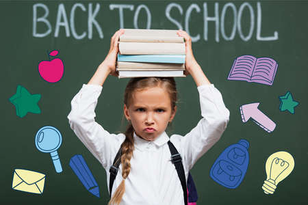 selective focus of displeased schoolgirl holding books above head near chalkboard with back to school lettering and illustration
