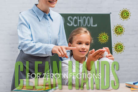 teacher pointing with finger at sanitizer near schoolgirl and clean hands for zero infections lettering in classroom