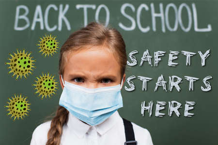 selective focus of displeased schoolgirl in medical mask near chalkboard and safety starts here lettering and virus illustration