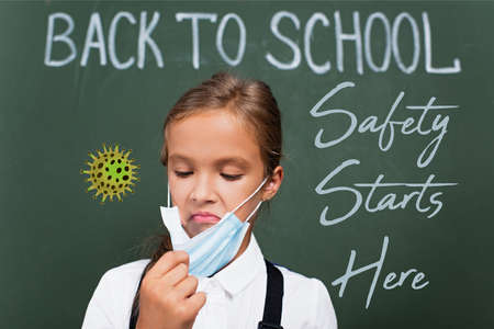 selective focus of displeased schoolgirl touching protective mask near chalkboard with safety starts here lettering in classroom 免版税图像