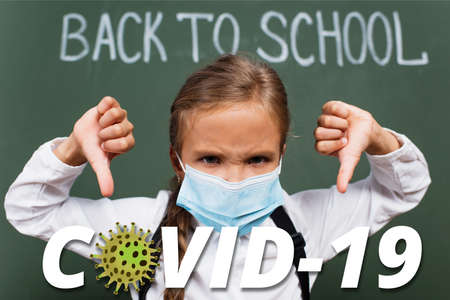 selective focus of displeased schoolgirl in medical mask showing thumbs down near chalkboard with inscription and covid-19 lettering in classroom