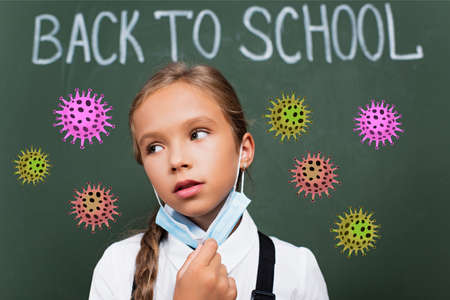 selective focus of exhausted schoolgirl taking off protective mask near chalkboard with back to school lettering and virus illustration