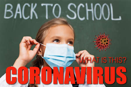 selective focus of schoolgirl wearing medical mask near chalkboard, what is this coronavirus lettering and virus illustration