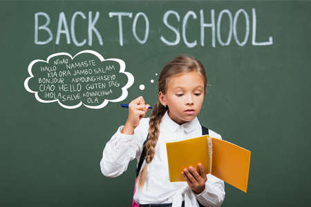 concentrated schoolgirl holding copy book and pen near chalkboard and greeting lettering in classroom