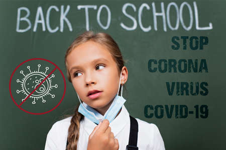 selective focus of exhausted schoolgirl taking off protective mask near chalkboard, stop corona, virus, covid-19 lettering and illustration