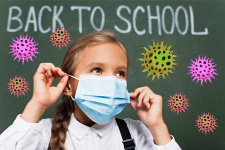 selective focus of schoolgirl wearing medical mask near back to school lettering on chalkboard and virus illustration