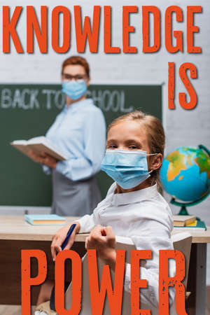 selective focus of schoolgirl in medical mask looking at camera while teacher standing near chalkboard and knowledge is power lettering