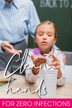selective focus of schoolgirl applying hand sanitizer near teacher and clean hands for zero infections lettering in classroom